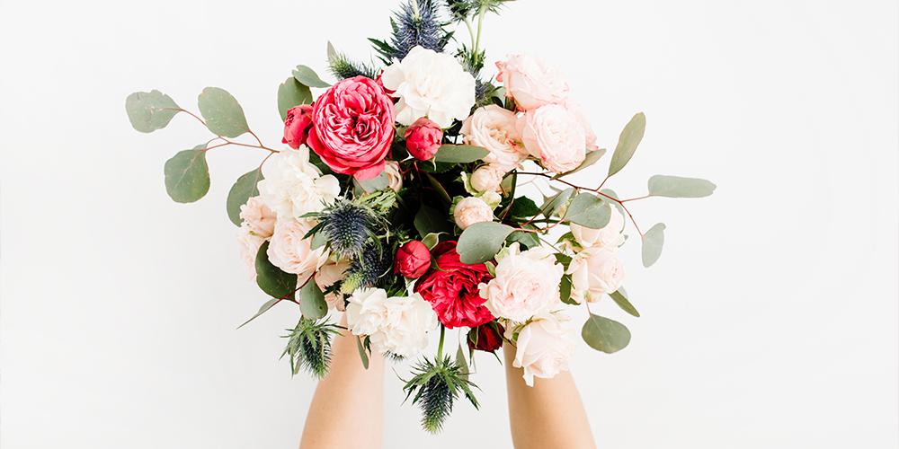 mano che tiene un mazzo di fiori